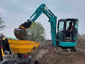 Kobelco Digger sat on soil loading a dumper